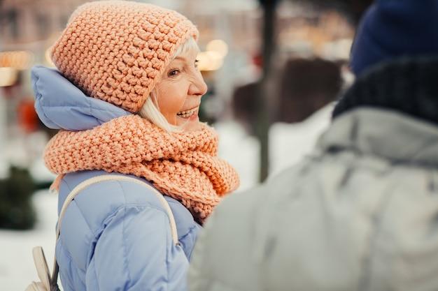 Close-up van een oudere vrouw in winterkleren die er gelukkig uitziet en glimlacht naar haar vriend