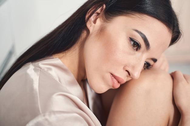 Close-up van een overstuur mooie dame die met de knieën in het gezicht zit en zich eenzaam en ongelukkig voelt