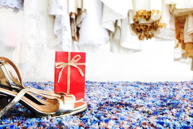 Close-up van een paar bruidschoenen in paskamer met huwelijkskledingachtergrond