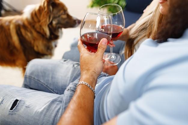 Close-up van een paar dat wijn drinkt op de bank met hun border collie-hond in de buurt