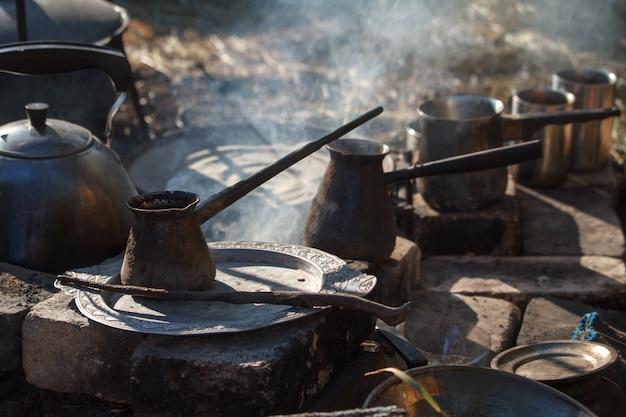 Close-up van een paar gerookte cezva op kampvuur voor koffie