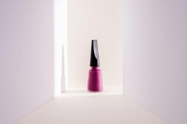 Close-up van een paarse nagellak tegen een witte