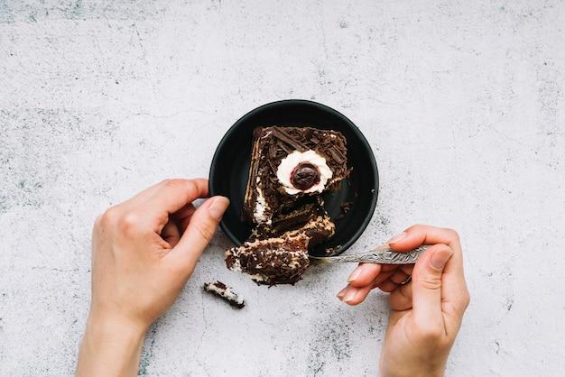 Close-up van een persoon die chocoladetaart met lepel op grungeachtergrond neemt