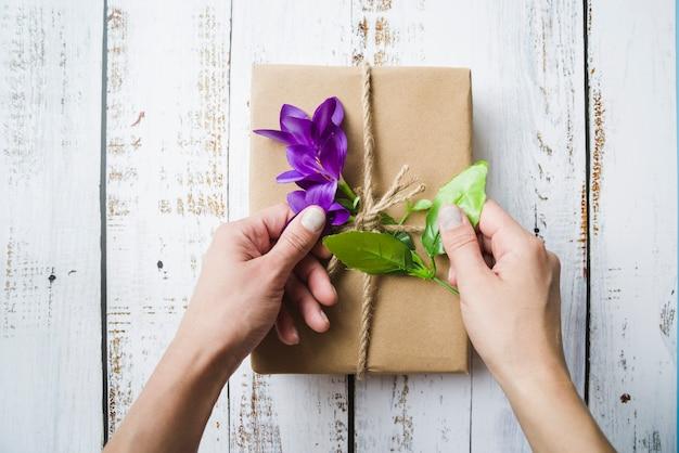 Close-up van een persoon die de bloemen op het ingepakte pakket raakt