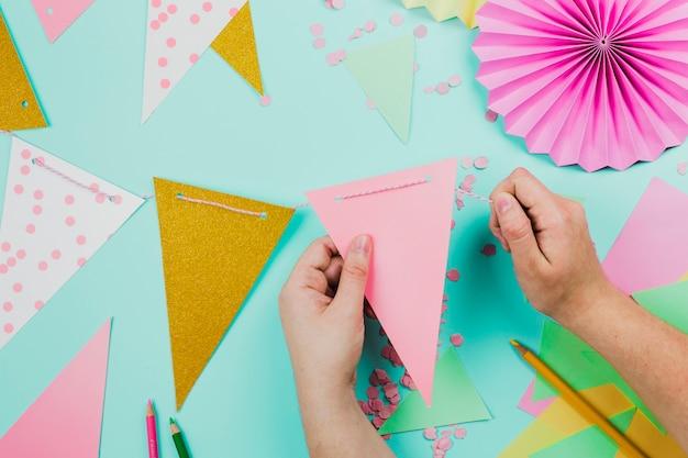 Close-up van een persoon die de bunting met driehoekig document en confettien op wintertalingsachtergrond voorbereidt