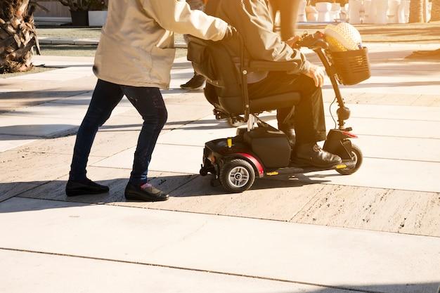 Close-up van een persoon die de mensenzitting over mobiliteitsscooter op straat duwt