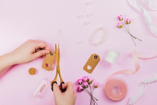 Close-up van een persoon die de tag met armband afsnijdt; kunstmatige rozen en lint op roze achtergrond