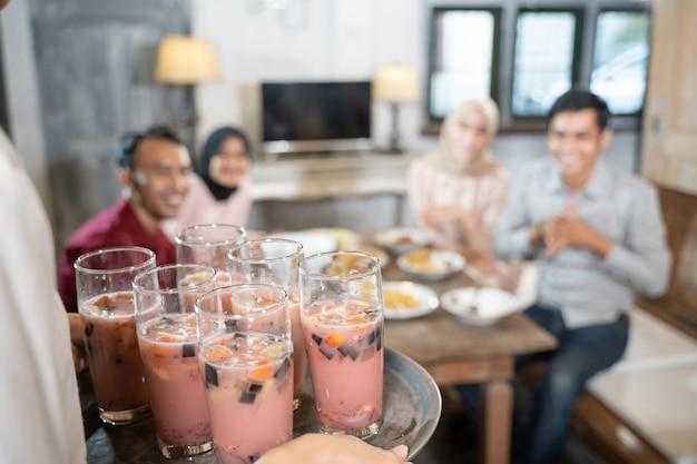 Close-up van een persoon die een dienblad met ijs in glazen draagt terwijl hij samen luncht in de eetkamer.