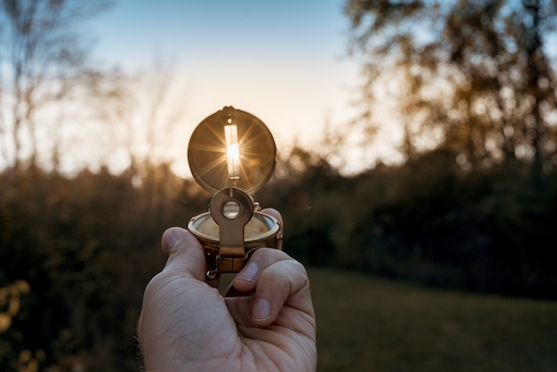 Close-up van een persoon die een kompas met zon houdt die door het gat glanst