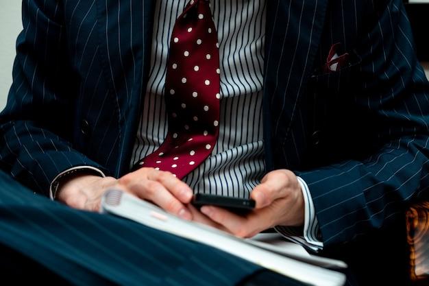 Close-up van een persoon die een kostuum draagt en een telefoon met een notitieboekje houdt