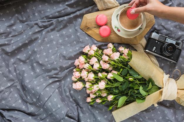Close-up van een persoon die makaron in koffie met camera en bloemboeket op tafelkleed onderdompelen