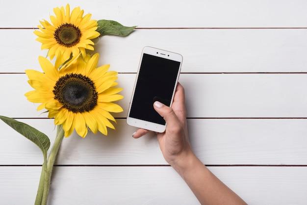 Close-up van een persoon die mobiele telefoon in de buurt van de gele zonnebloemen op witte houten tafel