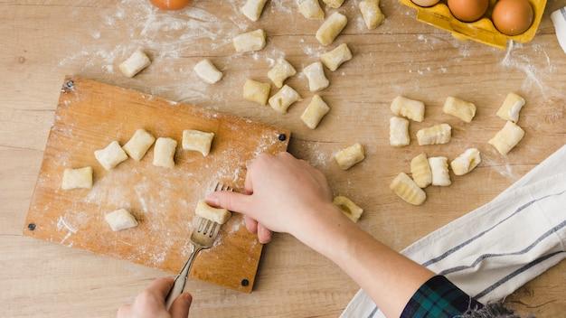 Close-up van een persoon die op het deeg van deeg met vork op hakbord drukt