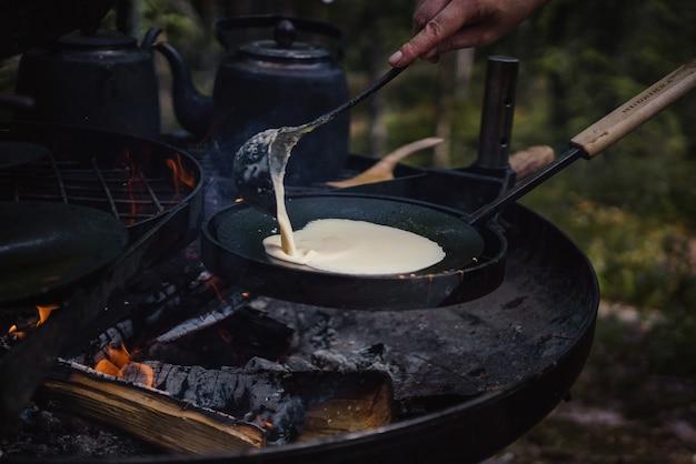 Close-up van een persoon die pannenkoeken kookt boven het kampvuur buitenshuis