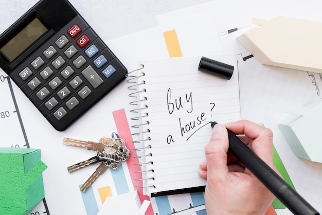 Close-up van een persoon die schrijft om een huis op spiraalvormige blocnote met sleutels te kopen; rekenmachine en huismodel