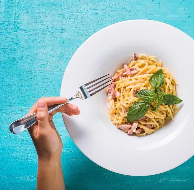 Close-up van een persoon die spaghetti met vork op turkooise achtergrond eet