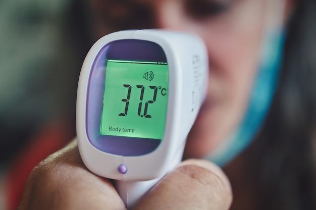 Close-up van een persoon die temperatuur meet met een digitale thermometer Gratis Foto