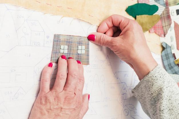 Close-up van een persoon die textielflard op tekeningsdocument over het bureau plakken