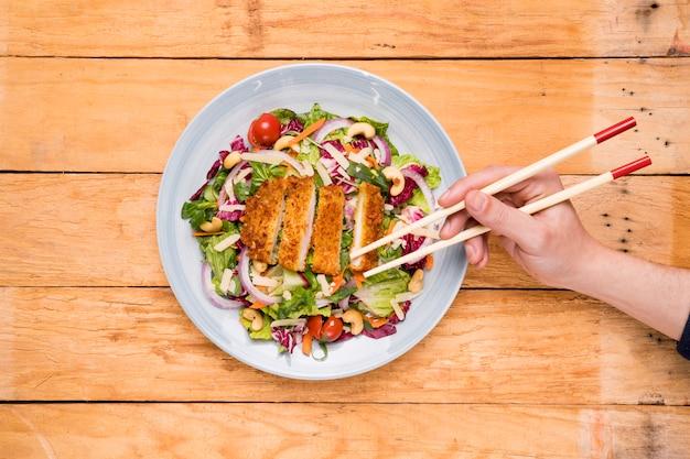 Close-up van een persoon die thais voedsel met eetstokjes op houten bureau plukt
