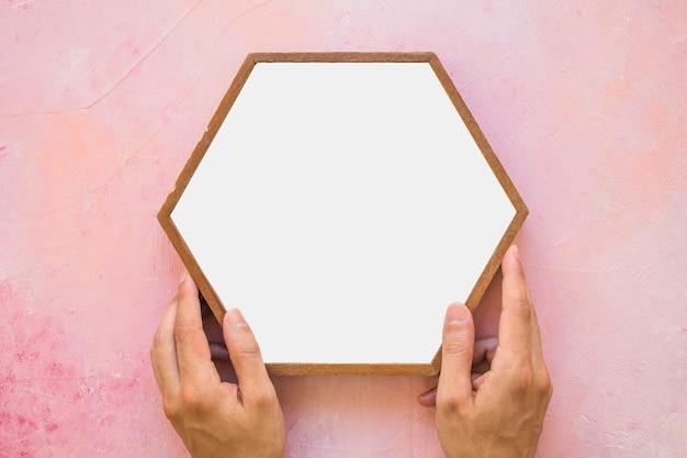 Close-up van een persoon die wit hexagon kader plaatsen op roze muur