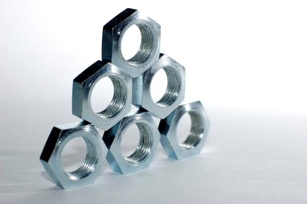 Close-up van een piramide van vijf verchroomde metalen moeren in de vorm van honingraten naast elkaar. het concept van het repareren van bevestigingsmiddelen en kleine productiedelen. copyspace