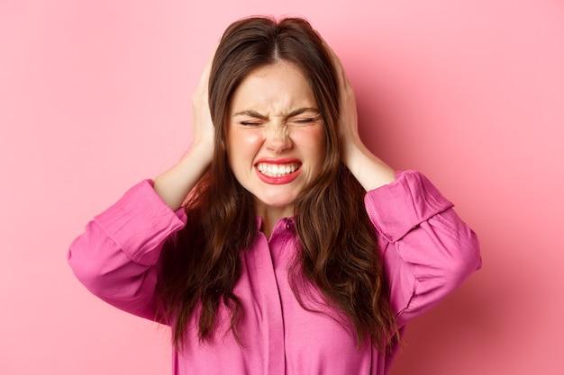 Close-up van een pissige en boze vrouw, grijnzende gehinderd, haar oren gesloten met handen van luid hinderlijk geluid, staande over roze muur.