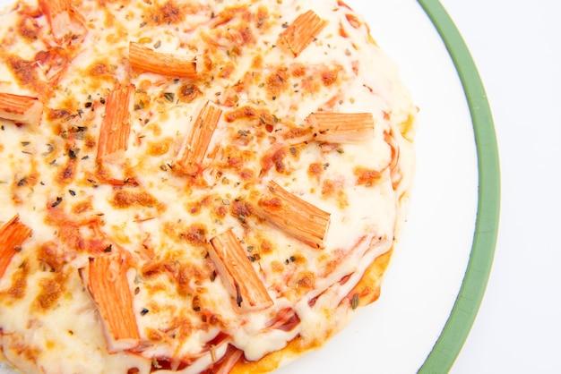 Close-up van een pizza in een kartonnen doos tegen op witte achtergrond pizza bezorging. pizzamenu.