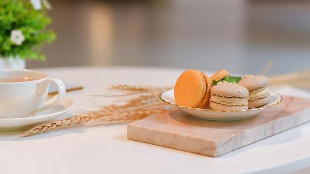 Close-up van een plaat van franse kleurrijke macarons en kopje thee op koffietafel in de woonkamer