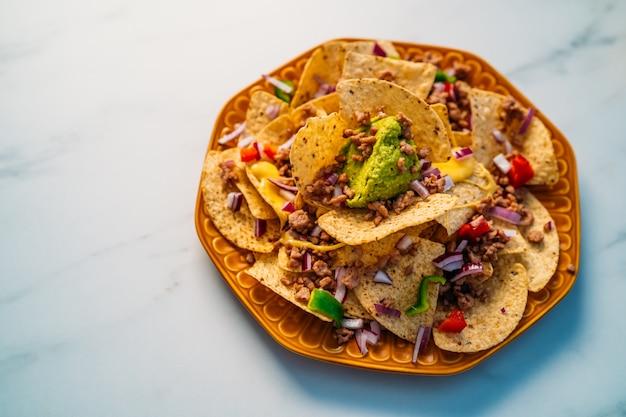 Close up van een plaat van heerlijke tortilla nachos maïschips met gesmolten kaassaus, rundergehakt, jalapeno pepers, rode ui, salsa en zure room met guacamole dip. bovenaanzicht