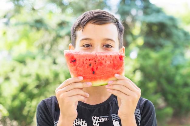 Close-up van een plak van de watermeloen van de jongensholding over zijn mond