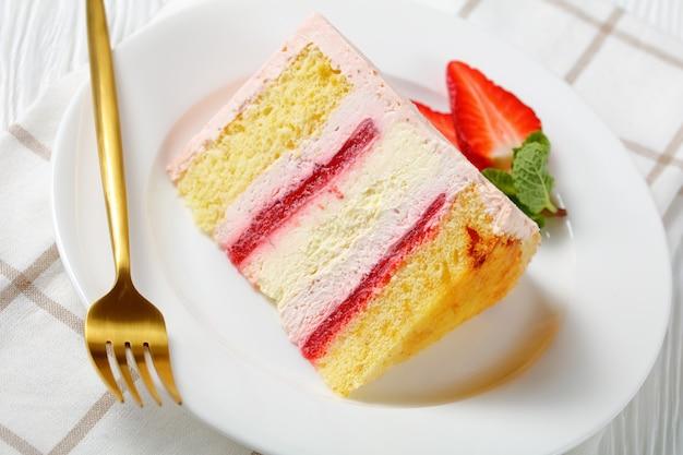 Close-up van een plak van een roze aardbeienkaastaart geserveerd met verse bessen op een witte plaat met gouden vork op een houten tafel