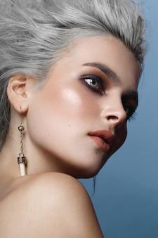 Close up van een portret van een jonge vrouw met grijs kapsel, smokey eyes, make-up, naakte schouders, op een blauwe achtergrond.