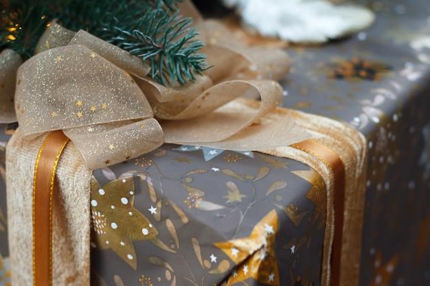 Close-up van een prachtig verpakt en vastgebonden met een gouden lint lint geschenk onder de kerstboom