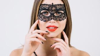 Close-up van een prachtige lachende vrouw in zwarte carnaval masker