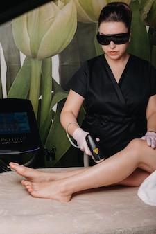 Close-up van een procedure voor het epileren van de benen in de salon gedaan door een professional in het zwart gekleed en met een moderne beschermende bril