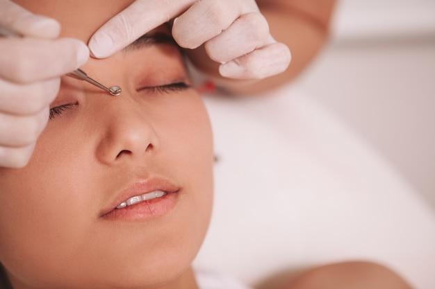 Close-up van een professionele schoonheidsspecialiste bijgesneden verwijderen van mee-eters op de neus van een vrouwelijke cliënt