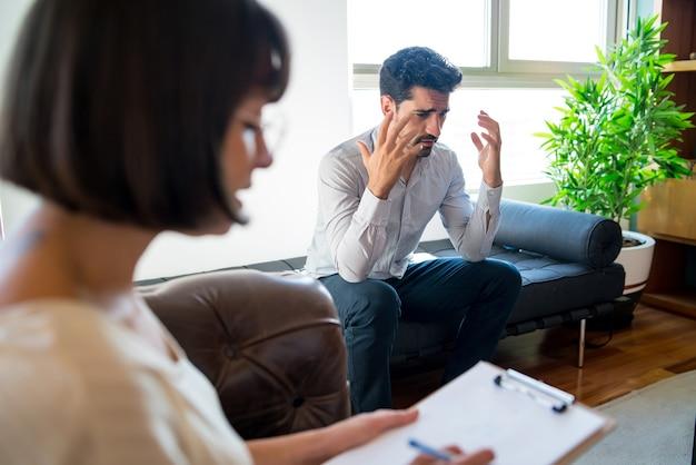 Close-up van een psycholoog die aantekeningen maakt op het klembord tijdens therapiesessie met haar bezorgde patiënt. psychologie en geestelijke gezondheidsconcept.