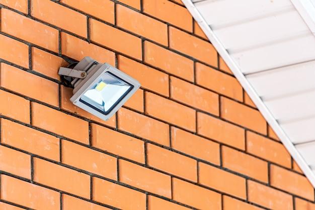 Close-up van een rechthoekige straatlamp op een bakstenen muur