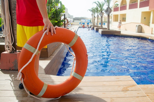 Close up van een reddingsboei ring met touw opgehouden door een badmeester met een zwembad op de achtergrond. badmeester tijdens werkconcept