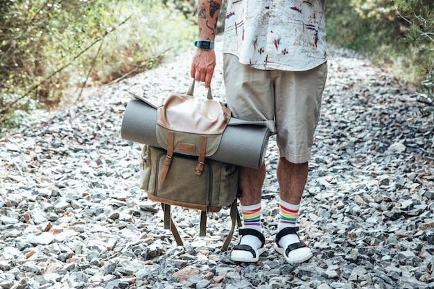 Close-up van een reiziger die een rugzak midden op de weg vasthoudt om te missen