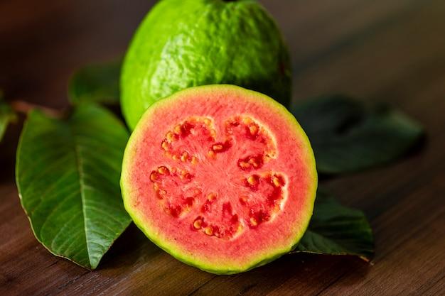 Close-up van een rode guave gesneden, verschillende guaves en groen blad