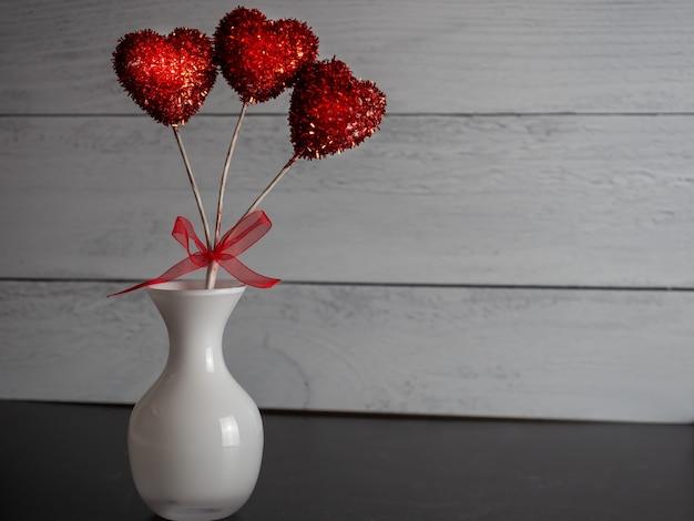 Close-up van een rode hartvormige decoratieve pop in een vaas tegen een grijze achtergrond