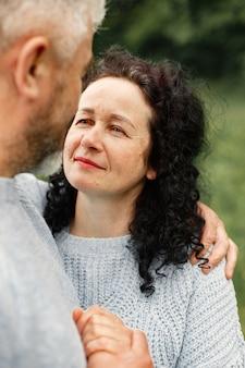 Close-up van een romantisch paar dat in het herfstpark staat en overdag knuffelt