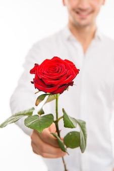 Close up van een romantische knappe man met een rode roos