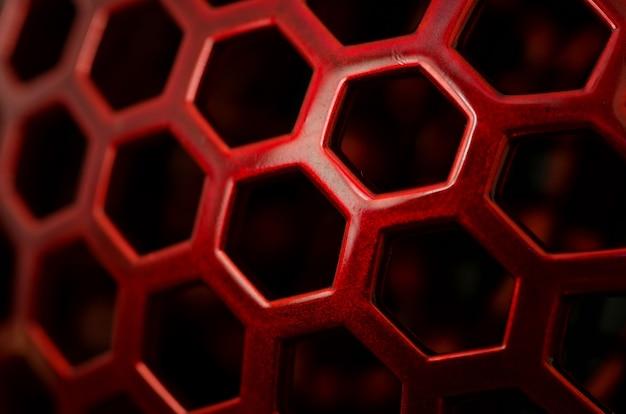 Close-up van een rood patroon met zeshoekige gaten