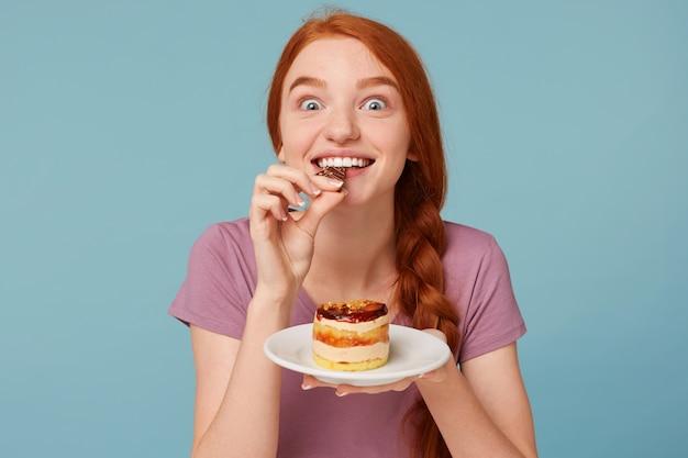Close-up van een roodharige vrouw die gretig een heerlijke cake proeft, een stuk chocolade bijt en een bord in haar handen houdt