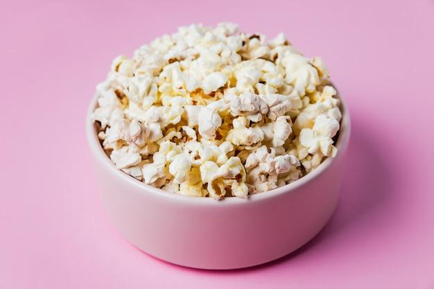 Close-up van een roze kom popcorn op roze oppervlak
