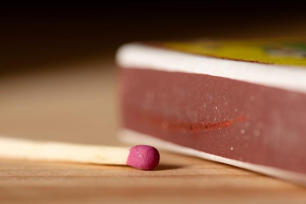 Close-up van een roze lucifer die op tafel bij de luciferdoos ligt
