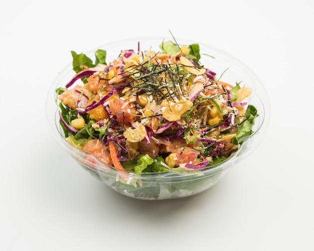 Close-up van een salade met paarse kool en vlees, maïs en gesneden groenten in een glazen kom