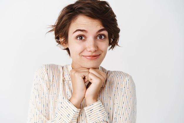 Close-up van een schattig en teder brunette meisje in een blouse die er romantisch uitziet, lacht en koket staart, staande tegen een witte muur